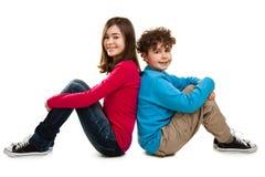 Ragazza e ragazzo che si siedono sul fondo bianco Fotografia Stock
