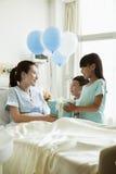 Ragazza e ragazzo che visitano la loro madre nell'ospedale, dando presente ed i palloni Fotografia Stock
