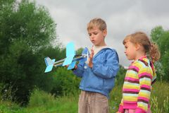 Ragazza e ragazzo con l'aeroplano del giocattolo in mani Immagini Stock
