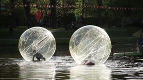 Ragazza e ragazzo nella palla dell'acqua nella piscina aperta video d archivio