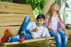 Ragazza e ragazzo sorridenti divertendosi al campo da giuoco Bambini che giocano all'aperto di estate Adolescenti su un'oscillazi Immagine Stock
