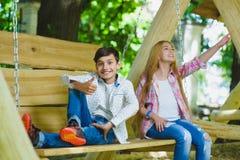 Ragazza e ragazzo sorridenti divertendosi al campo da giuoco Bambini che giocano all'aperto di estate Adolescenti su un'oscillazi Immagini Stock