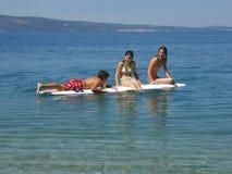 Ragazza e ragazzo sullo scrittorio praticante il surfing Immagini Stock Libere da Diritti