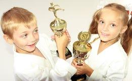 Ragazza e ragazzo in un kimono con un campionato che vincono nelle mani di Immagine Stock Libera da Diritti