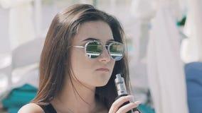 Ragazza in e-sigaretta di fumo nera, riposando sul salotto e guardando da parte archivi video