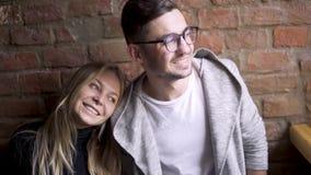 Ragazza e tipo in un caffè vicino ad una posa del muro di mattoni Sorridono, se esaminano Sono felici video d archivio