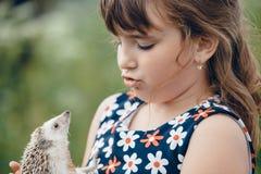 Ragazza e un istrice che se esamina Fotografia Stock