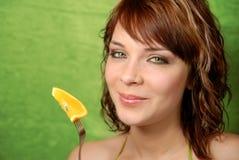 Ragazza ed arancio su una forcella Fotografia Stock