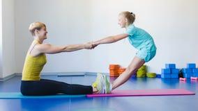 Ragazza ed istruttore o madre che fanno gli esercizi relativi alla ginnastica nella classe di forma fisica video d archivio