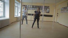 Ragazza ed uomini che ballano la plastica della striscia in video del metraggio delle azione dello studio di ballo video d archivio
