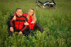 Ragazza ed uomo del motociclista che si siedono sull'erba vicino alla a Fotografia Stock Libera da Diritti