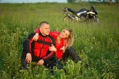 Ragazza ed uomo del motociclista che si siedono sull'erba vicino alla a Immagini Stock Libere da Diritti