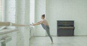 Ragazza elegante che fa gamba che allunga esercizio alla sbarra video d archivio