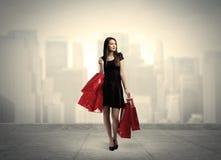 Ragazza elegante della città con i sacchetti della spesa rossi Fotografia Stock Libera da Diritti