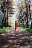 Ragazza elegante in un vestito rosso che cammina nel parco Immagini Stock