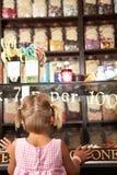 Ragazza emozionante che si leva in piedi nel negozio dolce Immagini Stock Libere da Diritti