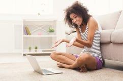 Ragazza emozionante con il computer portatile che si siede sul pavimento Immagini Stock