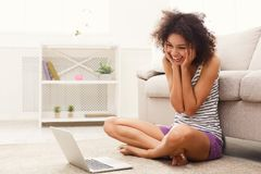 Ragazza emozionante con il computer portatile che si siede sul pavimento Fotografia Stock