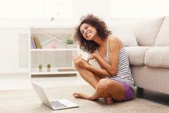 Ragazza emozionante con il computer portatile che si siede sul pavimento Fotografie Stock