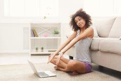 Ragazza emozionante con il computer portatile che si siede sul pavimento Fotografia Stock Libera da Diritti