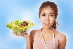 Ragazza esile asiatica con nastro adesivo ed insalata di misurazione Fotografia Stock