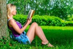Ragazza esile che legge un libro che si siede vicino all'albero Immagini Stock Libere da Diritti