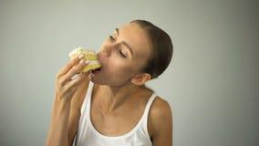 Ragazza esile che mangia ardentemente dolce, stante a dieta e morente di fame, mancanza di autodisciplina archivi video