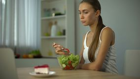 Ragazza esile che mangia insalata ma che ha bisogno dolce, tendenza di modo essere snello, dieta video d archivio
