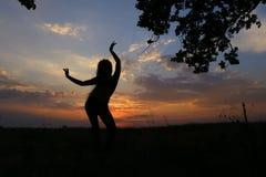 Ragazza esile che mostra le varie pose e che balla in un campo all'aperto Fotografie Stock