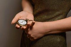 Ragazza esile che tiene un orologio da tasca d'annata Immagine Stock