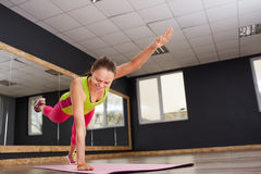 Ragazza esile dell'atleta della giovane donna di forma fisica che fa esercizio con le gambe sulla stuoia rosa di yoga Fotografia Stock Libera da Diritti