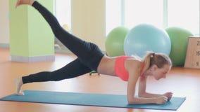 Ragazza esile dell'atleta della giovane donna di forma fisica che fa esercizio della plancia con l'incrocio di ginnastica del cro stock footage