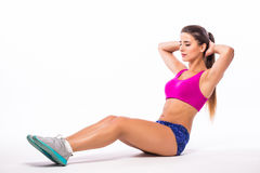 Ragazza esile dell'atleta della giovane donna di forma fisica che fa esercizio della plancia con le gambe Immagini Stock