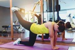 Ragazza esile dell'atleta della giovane donna di forma fisica che fa esercizio della plancia con Fotografie Stock