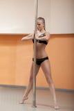 Ragazza esile sveglia che posa con il pilone nello studio di ballo Immagini Stock Libere da Diritti
