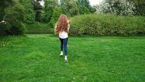 Ragazza europea con funzionamento lungo dei capelli ricci nel parco con le bolle di sapone Capelli molto lunghi che fluttuano nel video d archivio