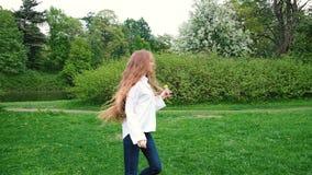 Ragazza europea con funzionamento lungo dei capelli ricci nel parco Capelli molto lunghi che fluttuano nel vento, movimento lento stock footage