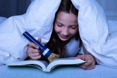 Ragazza facendo uso della torcia elettrica mentre libro di lettura fotografia stock libera da diritti