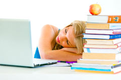 Ragazza faticosa che dorme sulla tabella con il computer portatile Fotografia Stock Libera da Diritti