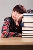 Ragazza faticosa dell'allievo che riposa sulla pila di libri Immagini Stock