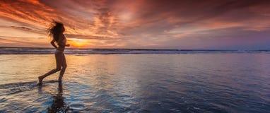 Ragazza fatta funzionare sulla spiaggia al tramonto immagine stock