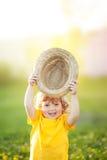 Ragazza felice adorabile con il cappello dello staw, piccolo agricoltore del todder Immagine Stock