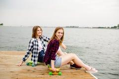Ragazza felice allegra del pattinatore due in attrezzatura dei pantaloni a vita bassa che ha seduta su un pilastro di legno duran fotografia stock