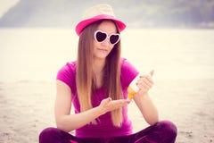 Ragazza felice in cappello di paglia ed occhiali da sole facendo uso della lozione del sole, protezione del sole sulla spiaggia Fotografia Stock Libera da Diritti