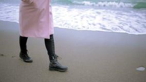 Ragazza felice in cappotto rosa vicino al mare durante la tempesta Il mare lava le sue orme nella sabbia video d archivio