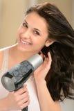 Ragazza felice che asciuga col phon i suoi capelli Fotografia Stock Libera da Diritti