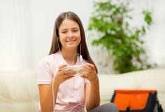 Ragazza felice che ascolta la musica dal telefono cellulare Immagini Stock