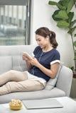 Ragazza felice che ascolta la musica dal telefono cellulare che si siede su uno strato a casa fotografia stock