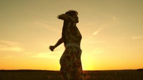 Ragazza felice che ascolta la musica e che balla nei raggi di bello tramonto contro il cielo ragazza in cuffie e stock footage