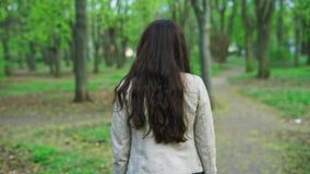Ragazza felice che cammina e che gira intorno con un sorriso nel parco video d archivio